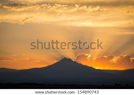 Dramatic sunset rays behind silhouette of of mountain - stock photo
