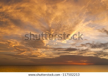 Dramatic sunset sky with clouds over ocean. - stock photo