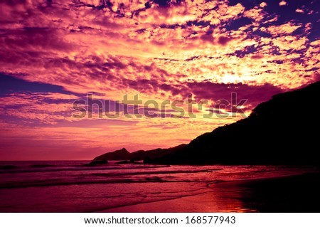 Dramatic Tropical Sunset at Lopes Mendes Beach, Ilha Grande Island, Rio de Janeiro State, Brazil - stock photo