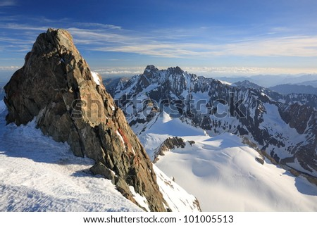 Dramatic view across snowy alpine peaks with rock pinnacle in foreground. - stock photo