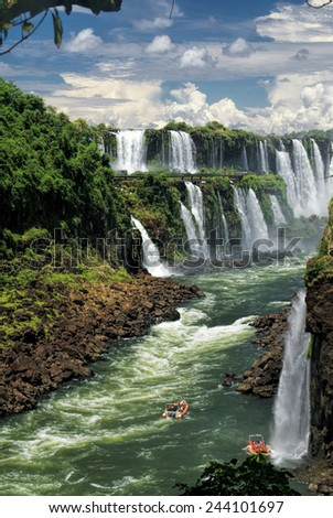 Dramatic view of Iguazu waterfalls in Argentina with tourist boats on the river          - stock photo