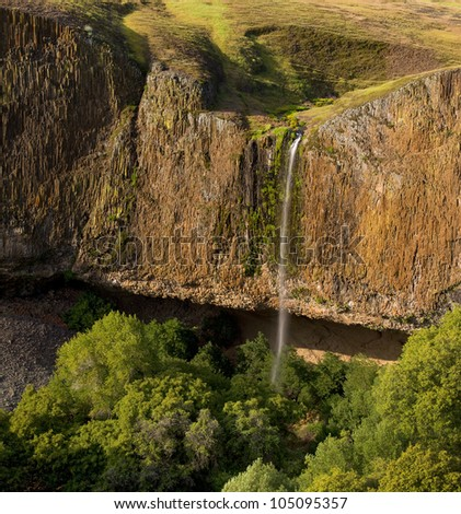 Dramatic waterfall cascades over majestic cliffs at sunset, with forest below and meadows above - stock photo