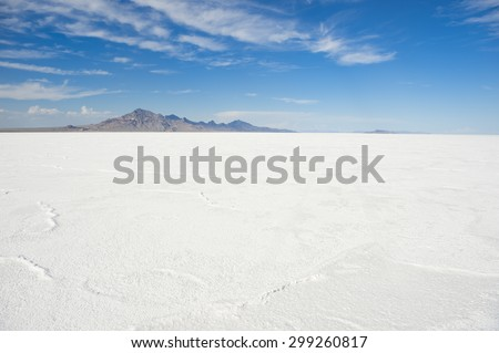 Dramatic white desert background of textured salt formations with rugged mountain range on the horizon - stock photo