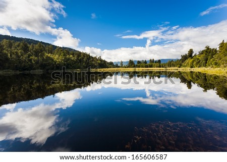 Dramtic reflections on Lake Matheson near Fox Glacier South Island New Zealand - stock photo