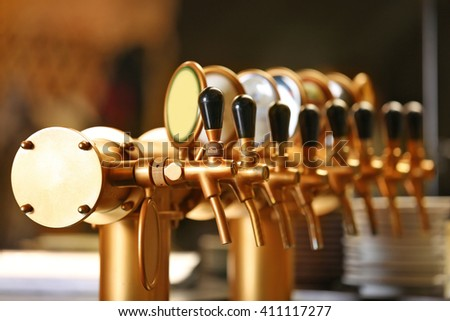Draught beer taps in a bar. - stock photo