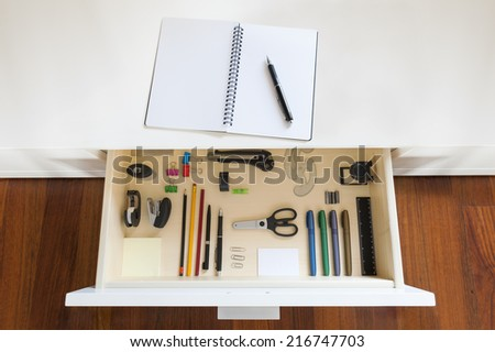 drawer with tools and accessories for drawing and office, with copybook and pen on desk - stock photo