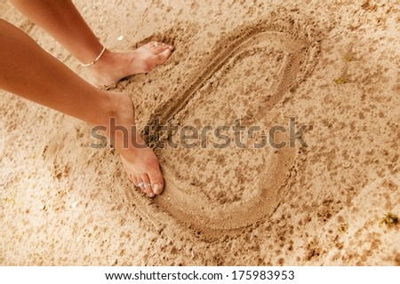 Drawing A Heart In The Sand - stock photo