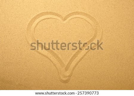 drawing a heart in the sand, blur - stock photo