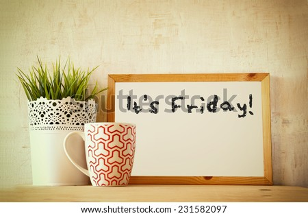 drawing board over wooden table with cup of coffee and flowerpot and the phrase it's friday - stock photo