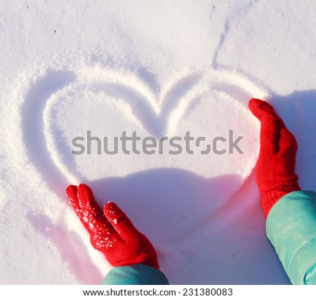 drawing heart on snow, love winter - stock photo