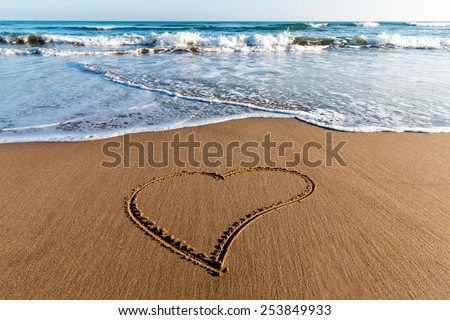 Drawing heart on the sand - stock photo