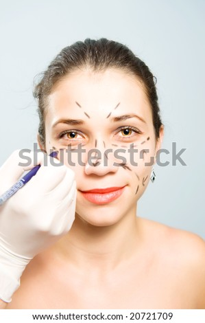 Drawing lines on a pretty Caucasian girl's face as marks for facial plastic surgery - stock photo