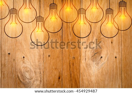 drawing of outline light bulbs glowing on wooden background. - stock photo