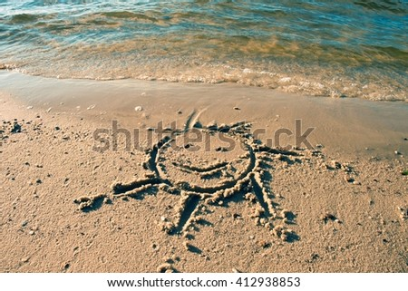 Drawing of sun in sand sand on exotic beach of bay - stock photo