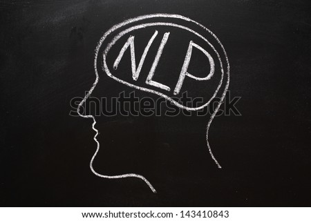 Drawing on a blackboard of a human head in profile with NLP on the brain. NLP is the acronym for Neuro-Linguistics Programming, often used in business and Psychotherapy for self improvement. - stock photo