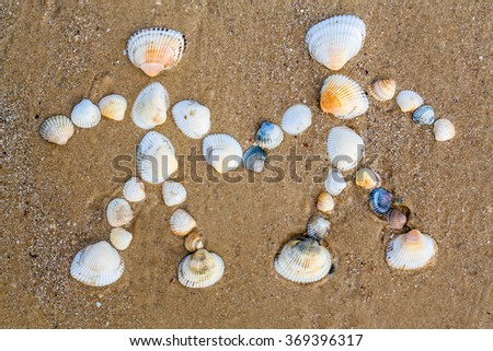 drawing on the sand couple in love made by seashells - stock photo