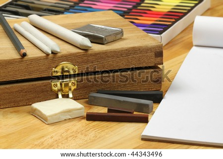 Drawing professional tools - paper stumps, charcoal pencil and sticks on wooden box. Pastels set - stock photo