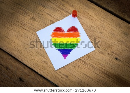 Drawing rainbow heart on paper pinned on a wooden background. - stock photo