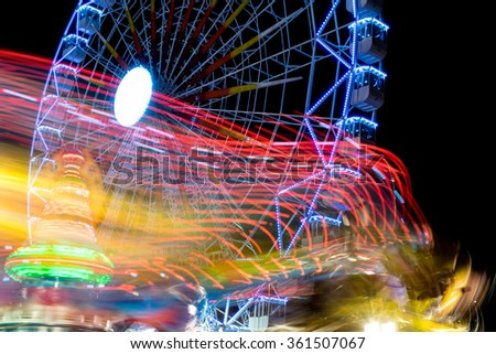 Drawings of lights in long exposure photo and fair ferris wheel background - stock photo