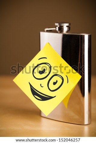Drawn smiling face on a post-it note sticked on a hip flask - stock photo