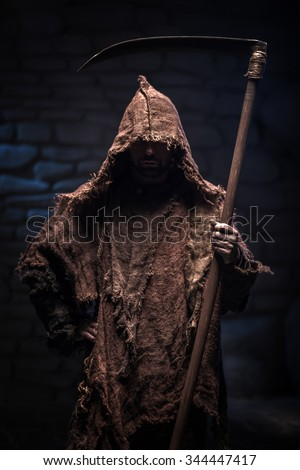 Dreadful death character is threatening with a scythe. He is standing and looking forward confidently - stock photo