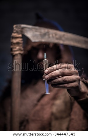 Dreadful death with a scythe is proposing you to shoot heroin. He is standing with confidence. Focus on a syringe - stock photo