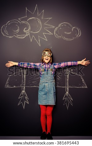 Dream flight. Cheerful girl imagines herself a pilot. Childhood. Fantasy, imagination. - stock photo