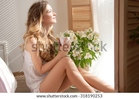 dream House.The sun is shining into the bedroom,she looks out the window.The lady sitting beside the bed,her hand near her head,she looks into the camera.Morning coffee, enjoyment.Woman and flowers - stock photo