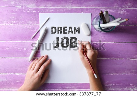 Dream job concept. Hands with color pencils and sheet of paper on wooden table - stock photo