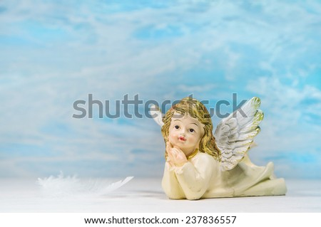 Dreaming angel on a blue background: greeting card for death, christening or communion. - stock photo