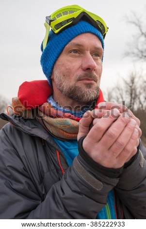 Dreaming bearded man, dressed as a mad pilot, drinking tea during recreation. Spring day on the coast. - stock photo