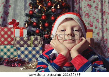 dreaming boy in Santa hat  in front of the fir tree.  New Year's holidays. - stock photo