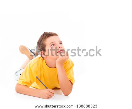 Dreaming boy lying on the floor and drawing with pencil - stock photo