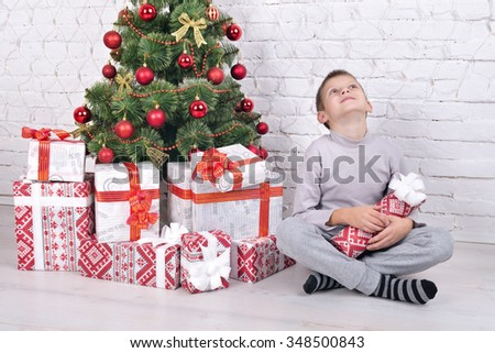 Dreaming boy with a gift sits near a Christmas tree with gifts. Christmas Tree. Christmas scene. Christmas gifts. Happy Children Opening Gift. - stock photo
