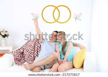 Dreaming concept. Loving couple sitting on sofa, on home interior background - stock photo