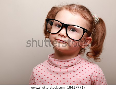 Dreaming cute girl in glasses looking up on copy space - stock photo
