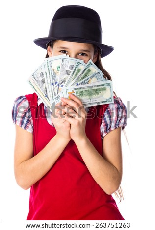 Dreaming girl in black hat hide face in money in hands, isolated on white - stock photo