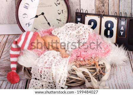 Dreaming Newborn Baby - naked in Hat on soft Blanket, with clock and board for birth time and birth date - stock photo