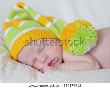 dreaming newborn wearing funny hat - stock photo