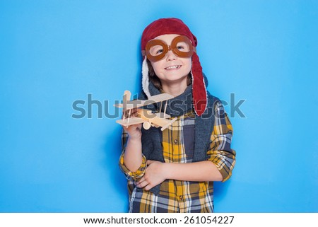 Dreaming of a big sky. Thoughtful of little boy in helmet playing with toy plane while standing against blue background - stock photo