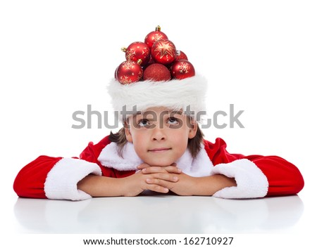Dreaming of christmas - boy with many decorations in his santa hat, isolated - stock photo