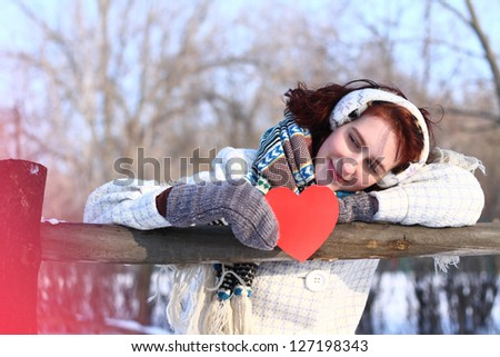 Dreaming winter girl holding red heart outdoors - stock photo