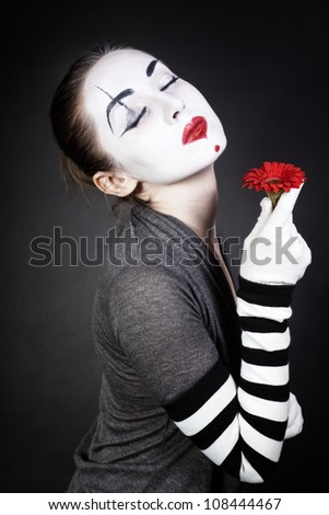 Dreaming woman mime with red flower on black background - stock photo
