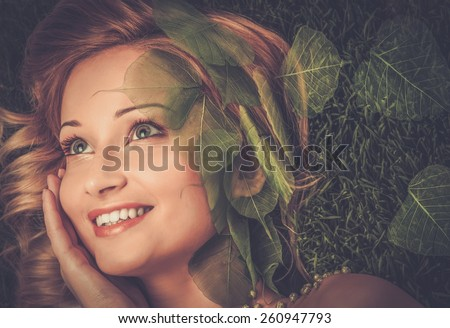 Dreaming young woman lying on a fresh spring grass  - stock photo