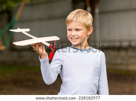 dreams, future, hobby, people and childhood concept - smiling little boy holding wooden airplane model in his hand outdoors - stock photo