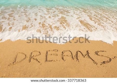 Dreams message on the beach sand - vacation and travel concept - stock photo