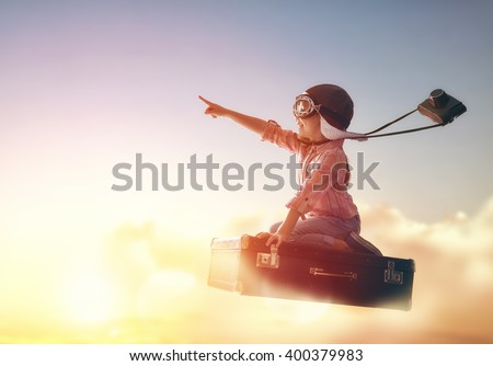 Dreams of travel! Child flying on a suitcase against the backdrop of a sunset. - stock photo