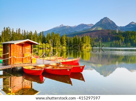 Dreamy boats stand near wooden bridge and a hut on a mountain lake on a spring day.Strbske Pleso lake, Slovakia, Tatra mountains - stock photo