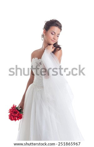 Dreamy bride posing with veil, isolated on white - stock photo