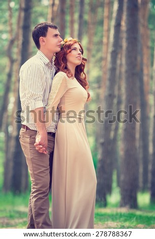 Dreamy couple in the park, stylish bride with groom dreamy looking up in the sky, love and fashion concept - stock photo